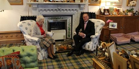 The Queen, wearing a Balmoral tartan skirt and surrounded by family photos, meets Prime Minister John Key in her Balmoral sitting room.