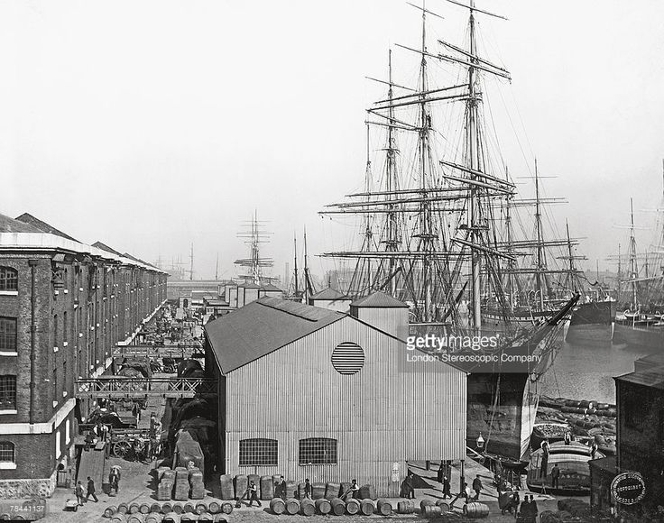 Cargo stacked by warehouses on the waterfront at a busy London dock where a large sailing ship is moored, circa 1893.