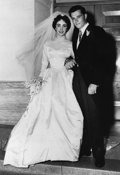 "In 1950, Liz Taylor took her first trip (of seven) down the aisle, marrying hotel heir Conrad ""Nicky"" Hilton in a Hollywood ceremony. Her silk, basque-waisted gown cost a then-staggering $1500 (almost $14,000 in today's dollars) to make and was a gift from her studio, MGM."