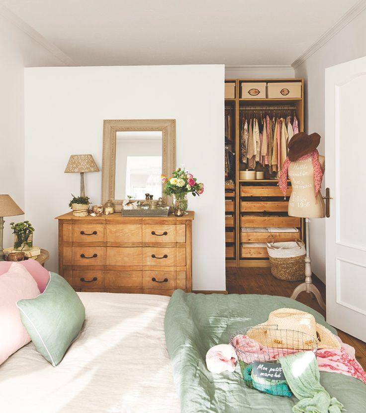 Dormitorio con vestidor abierto oculto tras un murete que no llega hasta el techo