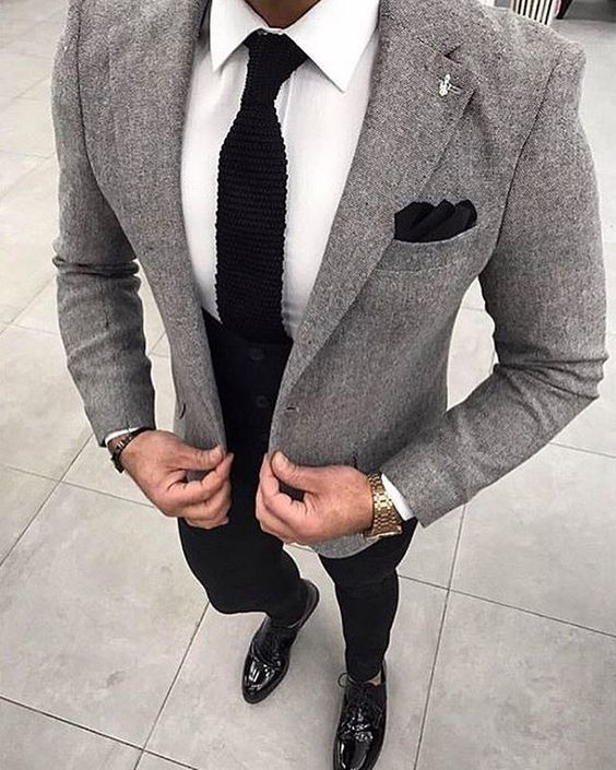 Pair a grey wool coat with black pants if you're going for a neat, stylish look. Turn your sartorial beast mode on and make black leather oxford shoes your footwear choice. Shop this look on Lookastic: https://lookastic.com/men/looks/blazer-dress-shirt-chinos/24006 — White Dress Shirt — Black Knit Tie — Black Pocket Square — Grey Wool Blazer — Dark Brown Bracelet — Gold Watch — Black Chinos — Black Leather Oxford Shoes