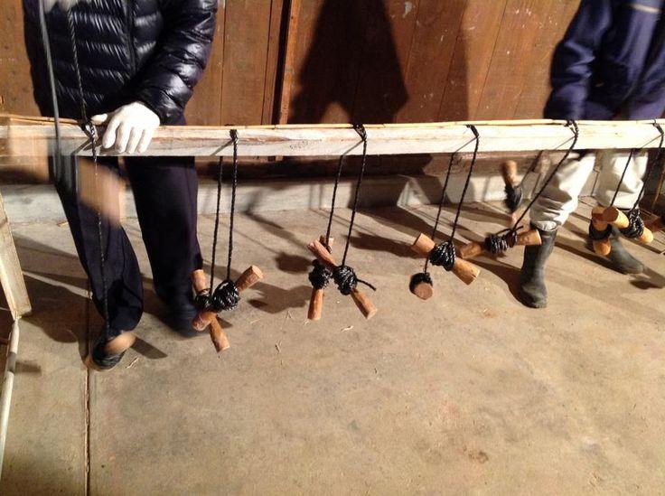 [4]まだ2本目です。 左から一つ置きに縄が交差されているのが、わかるでしょうか。 2本目以降は、一つおきに編んでいきます。 2本目は、左から1,3,5,7の場所を、次の3本目だと左から2,4,6,8の場所を編みます。 二人一組で、一人が4本の縄を担当します。 ヨシはササクレだって刺さることがあるので、軍手をして作業をされていました。