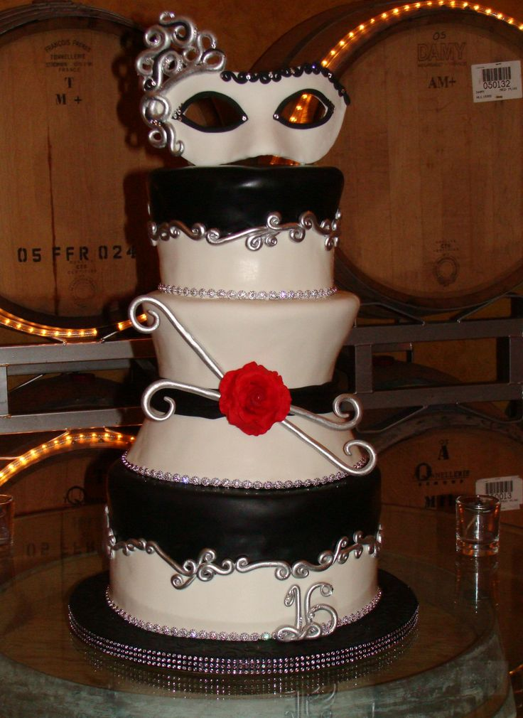 Masquerade cake made to celebrate a sweet 16. A black and white themed party for the girl in red. Mask and rose made out of fondant and adorned with Swarovski crystals. Created by Sugar Rush Delights.