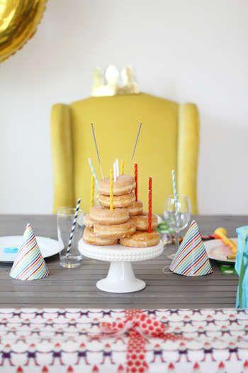 ドーナツを山のように積み上げてろうそくを飾るアイディア。トップには花火をセットすれば、パーティーが盛り上がること間違いなし!