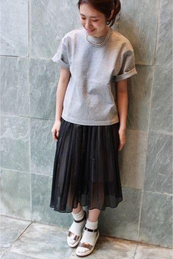 トップスからスカートにかけてのゆるやかなAラインシルエットが素敵な着こなし。 今年トレンドのコンフォートサンダルと白ソックスを合わせた足元がお洒落なスタイリングです。