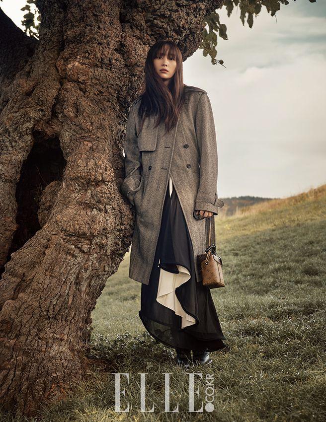 울 소재의 오버사이즈 트렌치코트와 불규칙한 헴라인의 블랙 & 화이트 롱 드레스, 스터드 장식의 카메라 박스 백, 앵클부츠는 모두 Louis Vuitton.