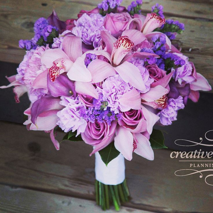 Beautiful bouquet in pinks and purples using pink cymbidium orchids, Coolwater roses, light purple carnations, and mini pink calla lilies. #weddingbouquet #weddingflowers #CalgaryWeddingFlorist #Banffweddingflorist