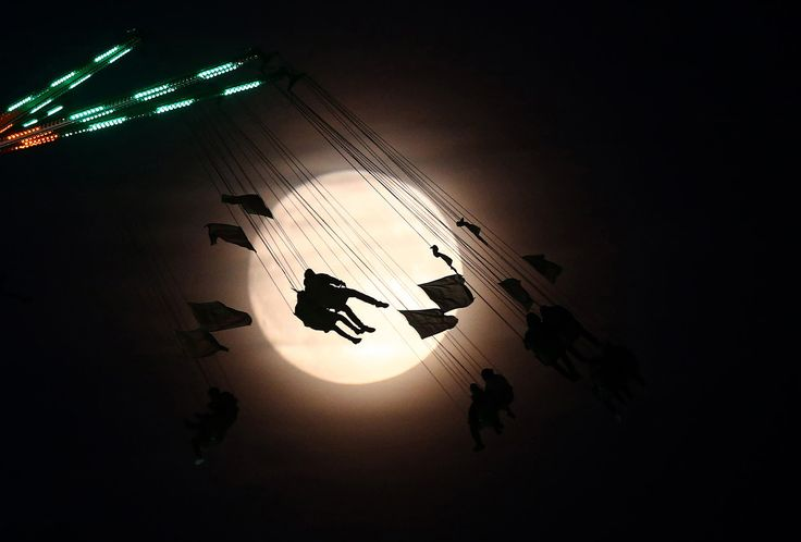 """People on a funfair ride are silhouetted against the moon a day before the """"supermoon"""" spectacle, in London, England, on November 13, 2016."""