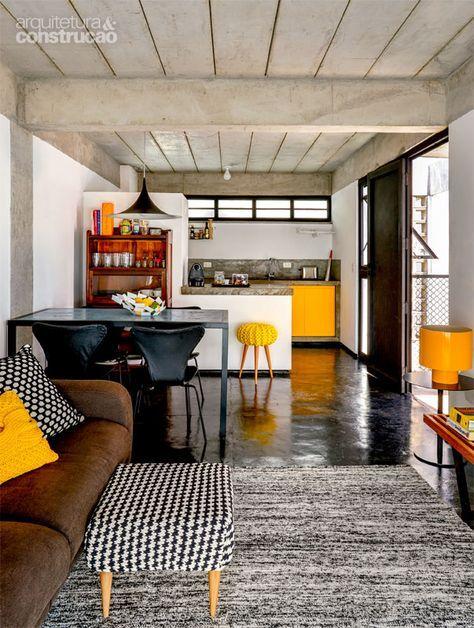 O preto distingue a casa de Tiago, cujo chão exibe cimento queimado com pigmento. Na cozinha, o contraste vem do armário de laminadoamarelo. As bancadas, em ambas as construções, são de concreto aparente polido. Almofadas e pufe de Zizi Maria, luminária amarela da FutonCompany, fruteira, vaso e objetos da Marché Art de Vie.