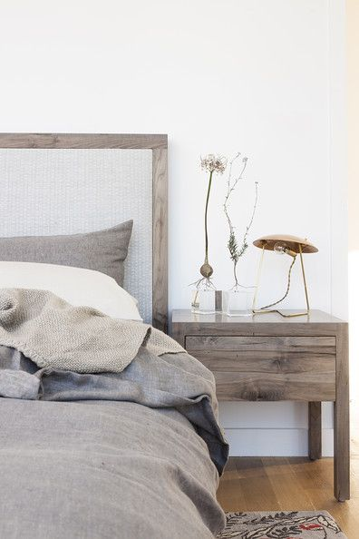 Organic sculptural forms juxtaposed with a contemporary table lamp on a bedside table. PS: how dreamy are these bed linens against that wood grain?
