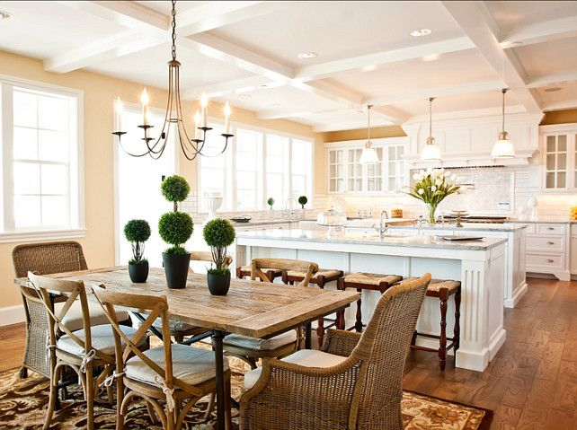 u-shaped kitchen w two islands, pendants over inner island, dining table behind stools w chandelier