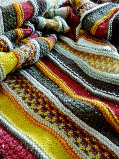 This striped afghan is a celebration of the New England countryside in autumn. The yellows and oranges of sugar maples and the incredible red of viburnum are tempered by the soft green of spruce needles and the perennial greens of pine. Worked in one piece with minimal finishing, it will keep you warm as you work on it