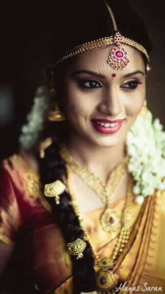 Traditional Southern Indian bride wearing bridal saree, jewellery and hairstyle. #BridalMakeup #TempleJewellery #MaangTikka
