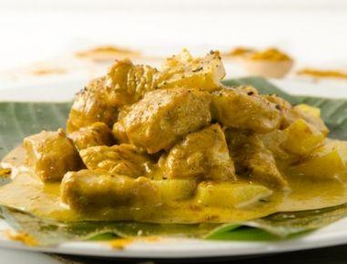 Für das Hühnercurry mit Ananas zunächst das Hühnerfleisch in Würfel schneiden. Ananas schälen und in Würfel schneiden. Ein Drittel der Kokosmilch
