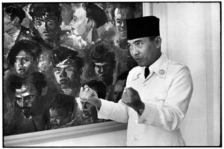 INDONESIA. 1949. Indonesian president SUKARNO at home.  The painting behind him depicts young Indonesian insurgents who died fighting the police. From Magnum Photos website.