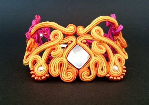 """Bransoletka wykonana metodą haftu sutasz. Fantazyjna i ażurowa bransoletka w optymistycznych letnich kolorach. Zdobi ją kamień z masy perłowej oraz szklane koraliki. Bransoletka jest odpowiednia na... Facebook: """"Soutache, beads, Shibori Cristallin, sutasz i koraliki"""""""