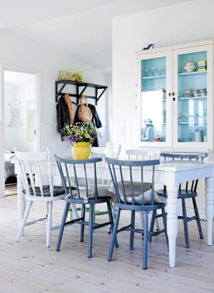 Spisestuen er lys og luftig med hvite vegger og tak, og et lyst tregulv. Både vitrineskapet og spisebordet går i ett med det hvite rommet. Beboerne har heller valgt å tilføre fargene i detaljene. Det blå glasset i vitrineskapet tar opp fargen fra de blå kjøkkenstolene, en gul vase med fargerike blomster er plassert på bordet, og en brunsvart jakkehylle henger i gangen.