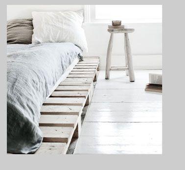 dans une chambre zen grise et blanche les palettes du lit sont lasures en gris