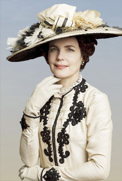 Downton Abbey's Elizabeth McGovern who plays Lady Cora wears a Victorian-inspired dress with a high neckline & detailing, paired with a wide-brimmed hat