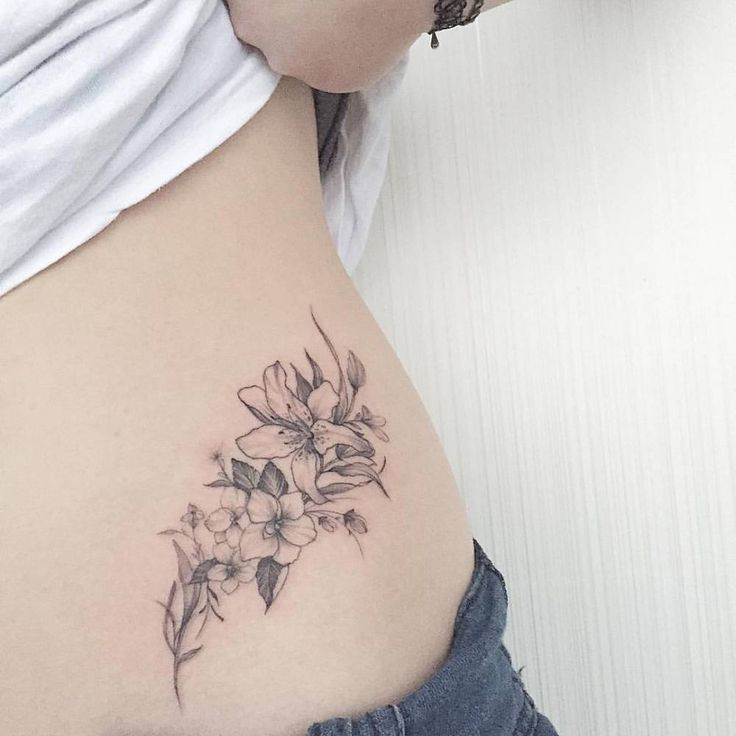 Fine line style violet and lily tattoo on the left side of the hip.