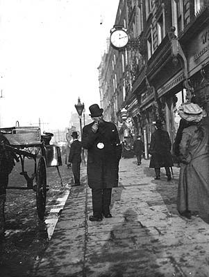 [Cabby walking and smoking pipe outside Nos. 32-33 Westmoreland Street]