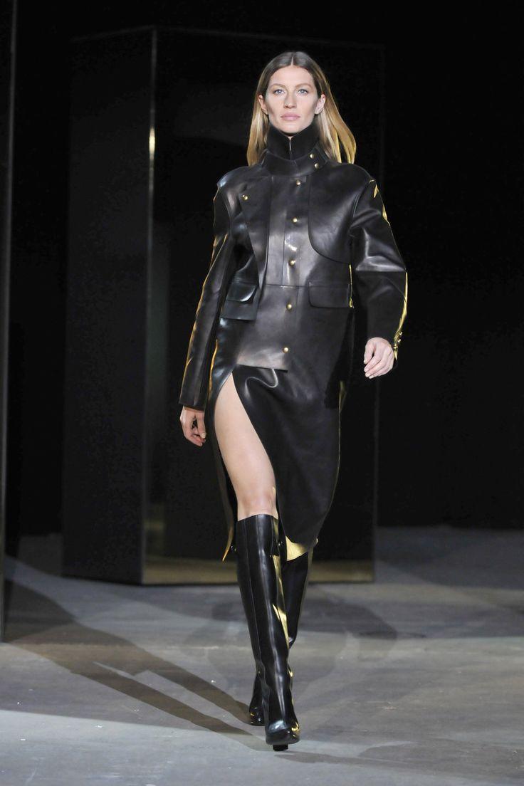 Gisele Bundchen modelo de pasarela saco negro de cuero botas negras de cuero cabello partido al medio