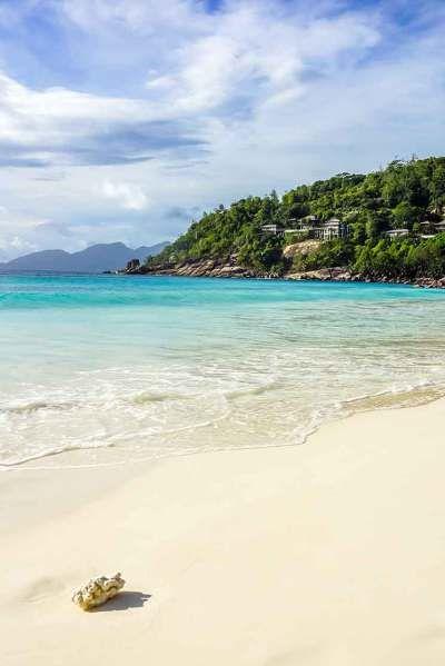 Praia do hotel Four Seasons Seychelles, um dos melhores hotéis em Seychelles, na Baie Lazare. Da varanda do bangalô vemos o mar azul-turquesa sem fim.