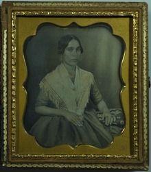 Aparecimento dos retratos de daguerreótipo. Senhora, com pose formal e por fim a fotografia, emoldurada .