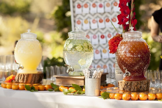 Rustic beverage bar with glass beverage dispensers of lemonade, cucumber water and iced tea.