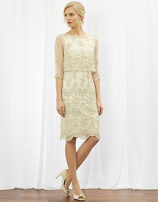 Featuring a sheer, intricately-detailed cape that can be worn in two distinct ways, or detached completely, this knee-length bridal gown is adorned with elaborate pearl and sequin embellishments, and gold metallic embroidery for extra sheen. The high, rounded neckline and v-shaped back create a flattering fit, while the scallop-edge hem adds an extra touch of luxe.