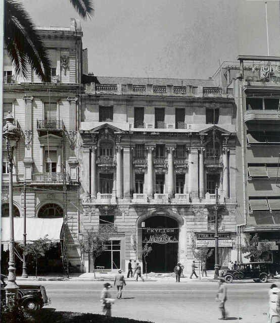 """""""Η πρώτη εκδοχή του κτηρίου Νικολούδη στην οδό Πανεπιστημίου, [σημ. όπως απεικόζεται στην φωτογραφία] για την οποία δεν υπάρχουν πλήρη στοιχεία, σχεδιάσθηκε το 1897 από τον ίδιο τον αρχιτέκτονα Αλέξανδρο Νικολούδη, σπουδαστή ακόμα της Ecole des Beaux-Arts στο Παρίσι."""