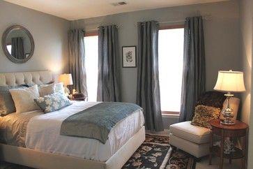 blue gray walls, dark curtains, white bed.