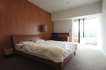 寝室は壁の1面を木で仕上げ、落ち着いた印象に。緑が目の前に広がるバルコニー付き