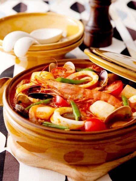 うどんとともに、いろいろな魚介や野菜をトマトスープで煮込んだ、南イタリア風鍋焼きうどん。海老、いか、あさり、里芋……具だくさんのアツアツを鍋ごと食卓へ。食べる際にブラックペッパーとパルミジャーノ・レッジャーノをふれば、風味がぐんとアップ。|『ELLE a table』はおしゃれで簡単なレシピが満載!