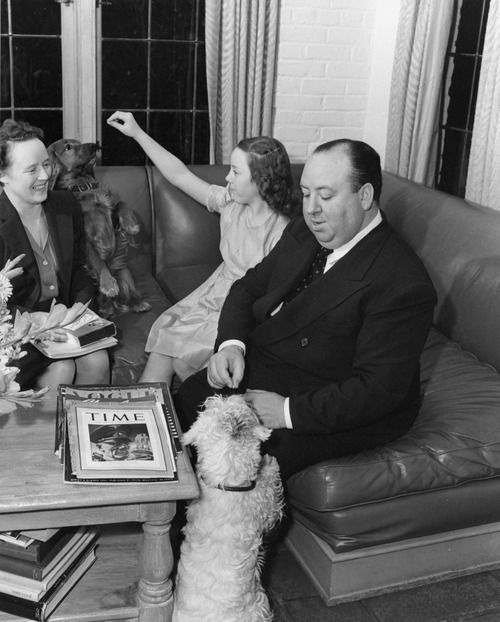 Alfred Hitchcock, wife Alma Reville, daughter Patricia Hitchcock, and dog at home ca. 1941.