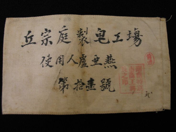 """This white arm band was likely warn by a World War Two prisoner of war while working in a Japanese soap factory. The text is translated as - """"Soap Factory Worker / The Eleventh Worker"""" and features a red stamp factory seal. From the collection of the Air Force Museum of New Zealand."""