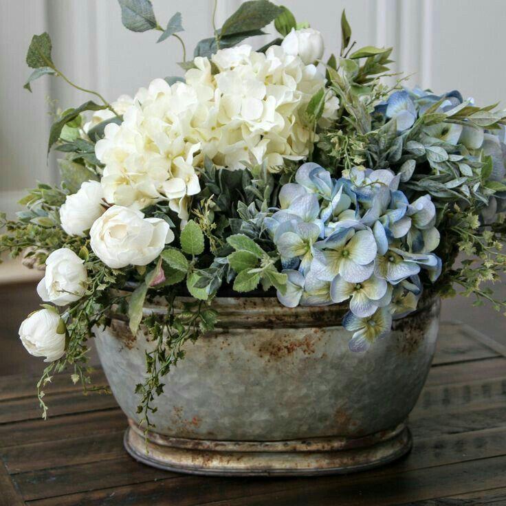 Sprühen Sie die ovale Metalldose auf Silber und füllen Sie sie mit gefälschten Blumen.