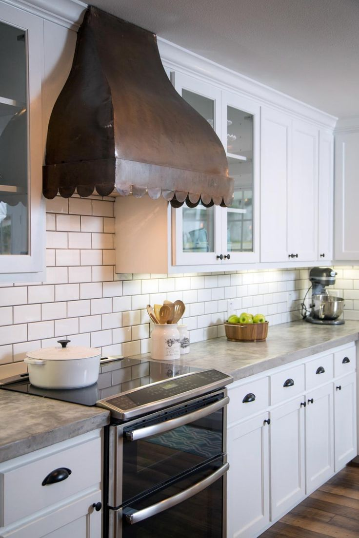 Modern accents, like the cement countertops and subway tile backsplash with a dark grout, contrast beautifully with the space's vintage look. See more from this episode.