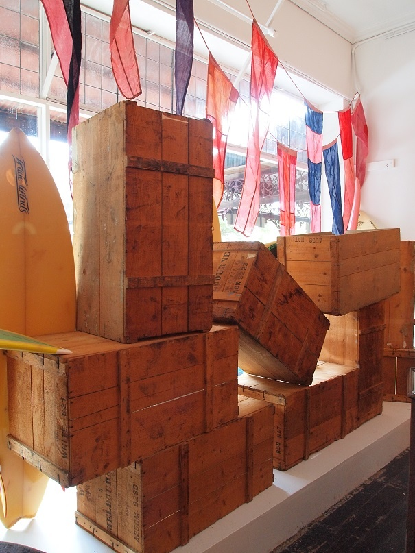 view of the back of our surfing window - dyed nautical signal flags, timber crates, filtered sunlight...