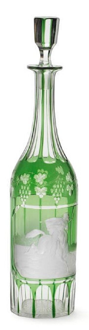 A pair of engraved decanters and stoppers by August Böhm Jr, circa 1870 Of slender or cylindrical bottle shape overlaid in green, the necks, bases and reverses cut with vertical flutes, the shoulders with borders of fruiting vines, the reserved panels engraved by August Böhm Jr, both signed A Böhm, one with an Arab horseman brandishing a scimitar, the other with a young man in a theatrical pose delivering a letter to a seated lady resting by a pedestal, 37.5cm high (minor chips) (4)