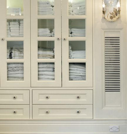 Built-in linen closet, white custom cabinetry with glass doors.