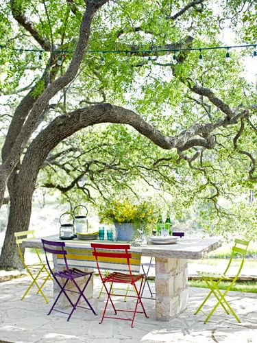 Metal folding chairs (from Barton Springs Nursery in Austin) offer colorful contrast to a table built out of Texas limestone.