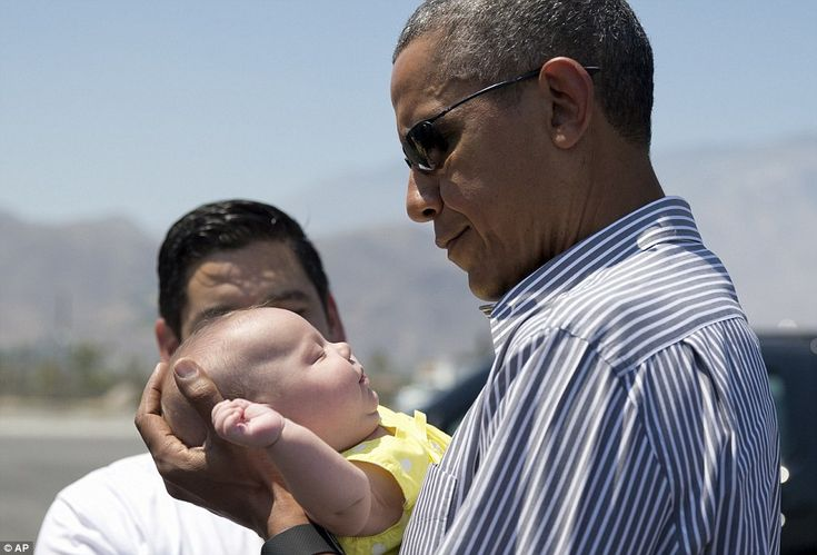Obama holds one of the twin daughters of Rep. Raul Ruiz, D-Calif., background, as he arriv...