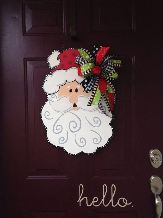 Bienvenue aux invités avec cette lunatique main peint accroche-porte Santa.  Il mesure 24 de haut x 16 de large, pulvérisé avec une couche de finition acrylique et orné dun arc de coordination.  Fabriqués à partir de 1/2 de bois blond et a un cintre