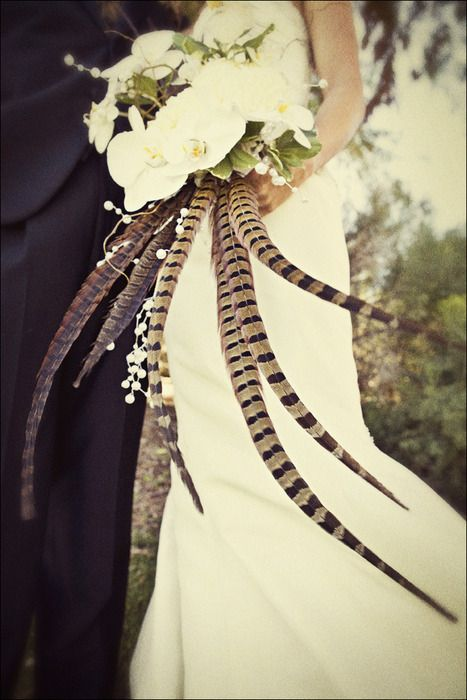Gorgeous, dramatic use of white flowers and feathers.