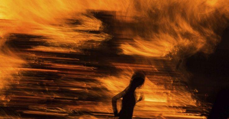 Folião fica próximo a fogueira durante as celebrações do solstício de verão em Freiburg, na Alemanha