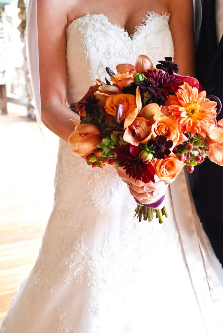 The bride's bouquet, above, contained various shades of orange roses, burgundy/plum and rust dahlias, hypericum berries, monkey tails, chocolate cosmos, calla lilies and coppery cymbidium orchids. The groom's boutonniere was a single orange rose with a foliage wrap, and the groomsmen wore monkey tails with hypericum berries and foliages.