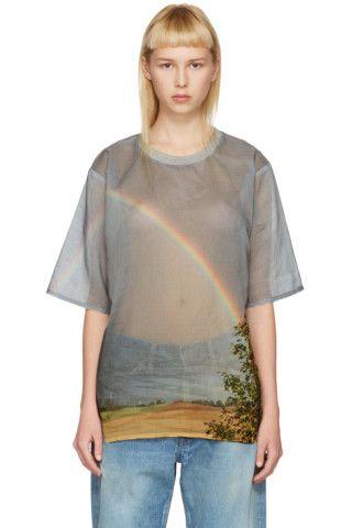 コットン織地の半袖 T シャツ。全体にマルチカラーのグラフィック模様。クルーネック カラーはグレーのリブ編み。裾にシルバートーンのロゴ プレート。同系色ステッチ。