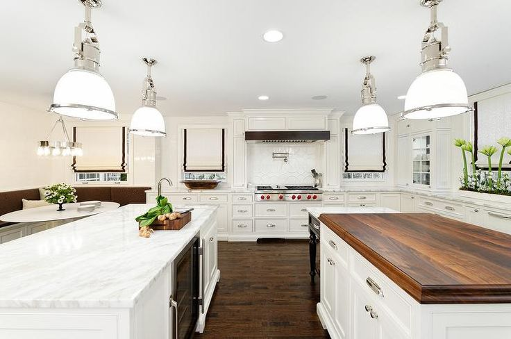 Beautiful kitchen features two center islands with one island topped with calcutta marble fitted with a prep sink and wine cooler and the second island topped with butcher block unified by Country Industrial Pendants with Glass Shades.