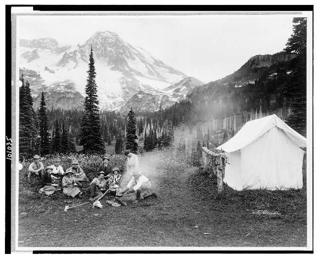 [Camping party of men and women cooking at campfire and eating near tent in Indian Henry, Mt. Rainier National Park, Washington]